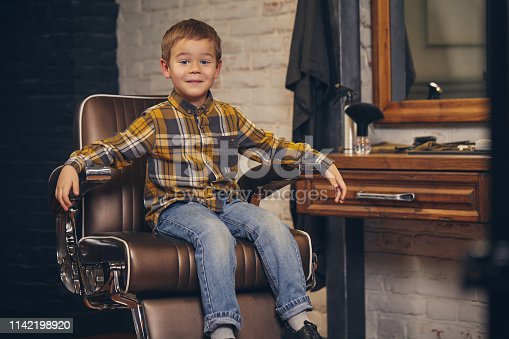 Portrait of a stylish little boy dressed in shirt and jeans sitting in a chair against the barber's workplace, he smiles and posing before camera
