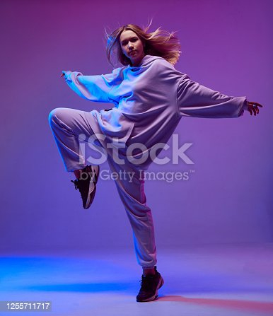 Portrait of a stylish young girl, cool dancing in a hoodie and with developing hair, on a neon background. High quality photo