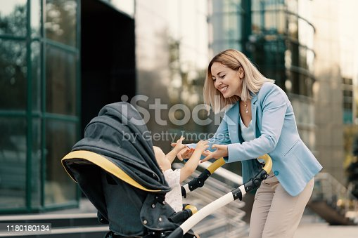 Portrait of a successful business woman in blue suit with baby. Business woman pushing baby stroller