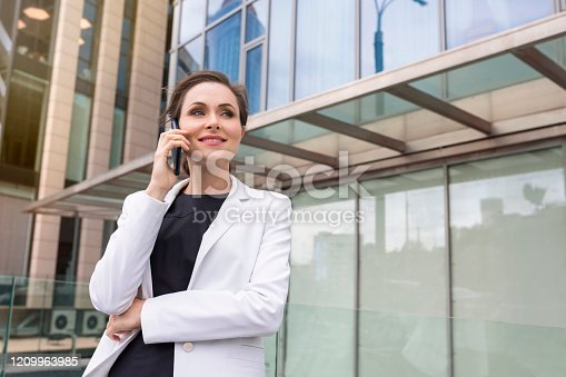 A portrait of a successful businesswoman speaking over a cell phone in the street. A manager, company employee.
