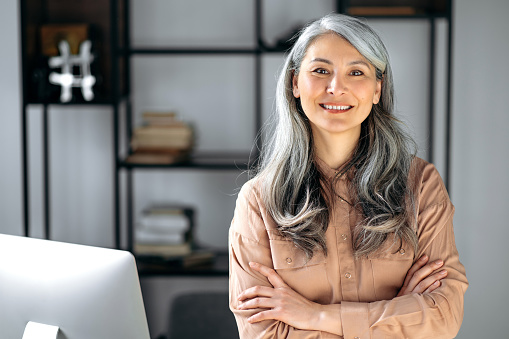 Portrait of a successful confident mature gray-haired lady, business woman, ceo or business tutor, standing in the office with arms crossed, looking and friendly smiling into the camera