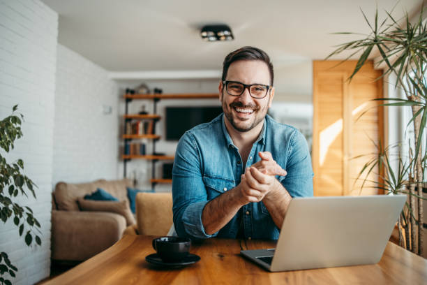 Portrait of a successful entrepreneur at cozy home office, smiling at camera. Portrait of a successful entrepreneur at cozy home office, smiling at camera. business laptop stock pictures, royalty-free photos & images