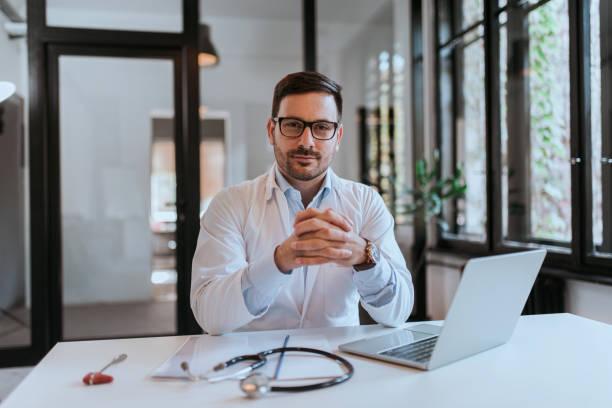Retrato de un médico guapo de éxito en el lugar de trabajo. - foto de stock