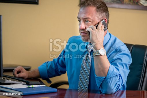1040964880 istock photo Portrait of a Successful Middle-Aged Man in Business Attire At his Desk Using His Phone 1200142234