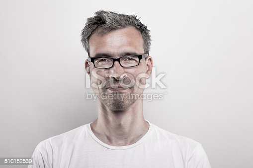 Facial portrait of a 45 years old man with grayed hair, stubbly beard and glasses