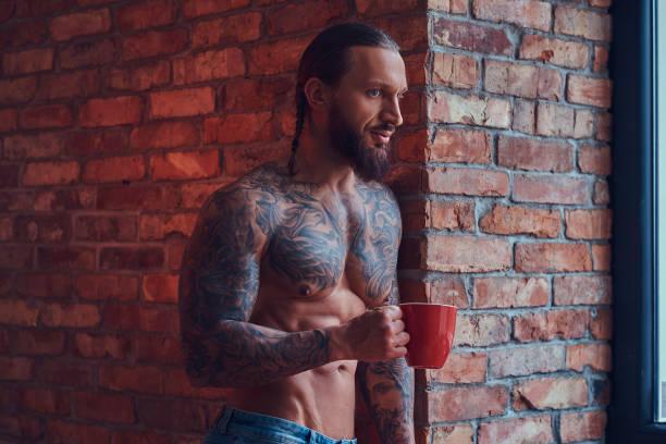 porträt von einem tätowierten shirtless rüden eine stilvolle frisur und bart, trinkt kaffee am morgen, lehnte sich gegen eine mauer in einem zimmer mit einem loft-interieur. - kaffeetasse tattoo stock-fotos und bilder
