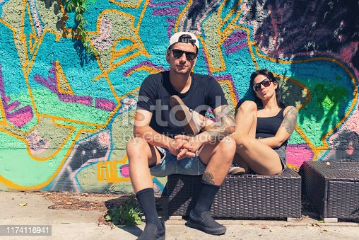 Portrait of a tattooed young couple in front of graffiti wall