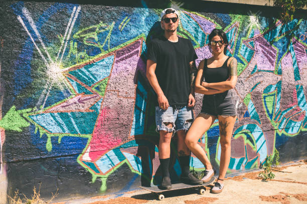 Portrait of a tattooed young couple in front of graffiti wall stock photo