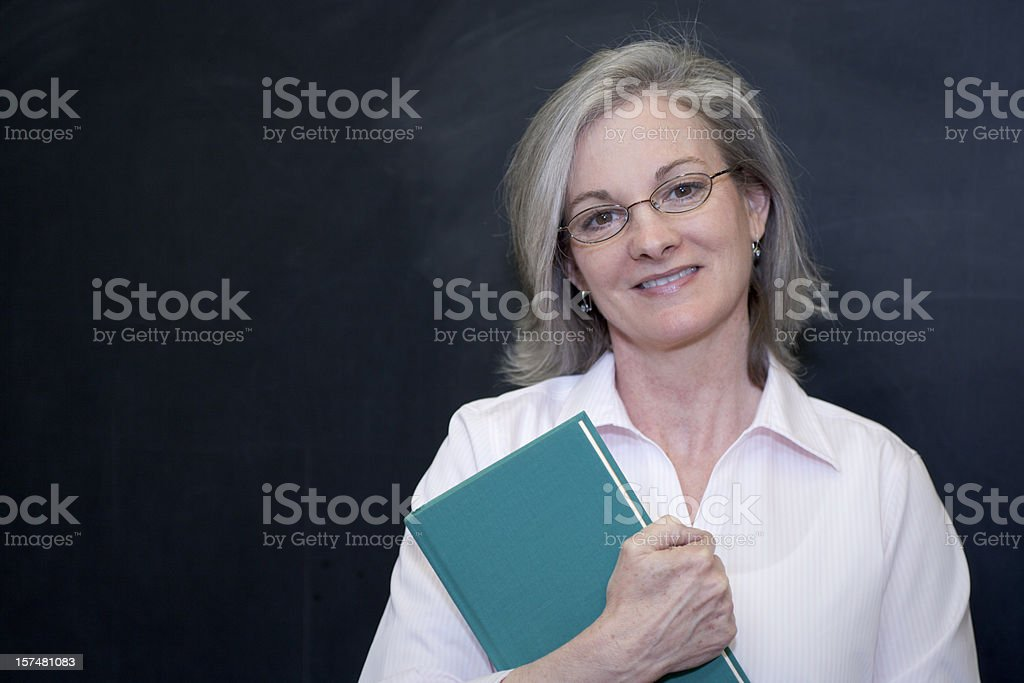 Portrait of a teacher standing in front of a blackboard royalty-free stock photo