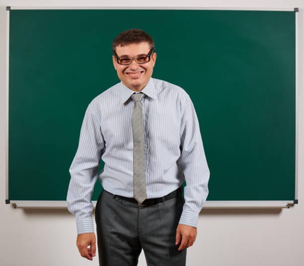 Retrato de un profesor con gafas pasadas de moda posando en el fondo de la pizarra - volver a la escuela y el concepto de educación - foto de stock