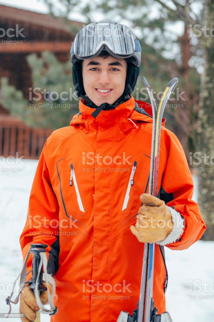 A mixed race teenage boy poses for a portrait in ski wear. He is...