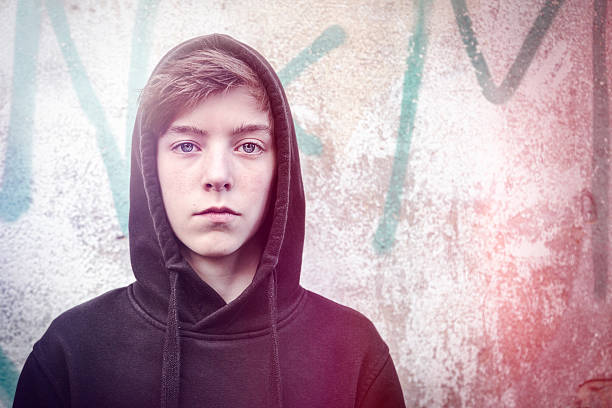 portrait of a teenage boy with black hoodie stock photo