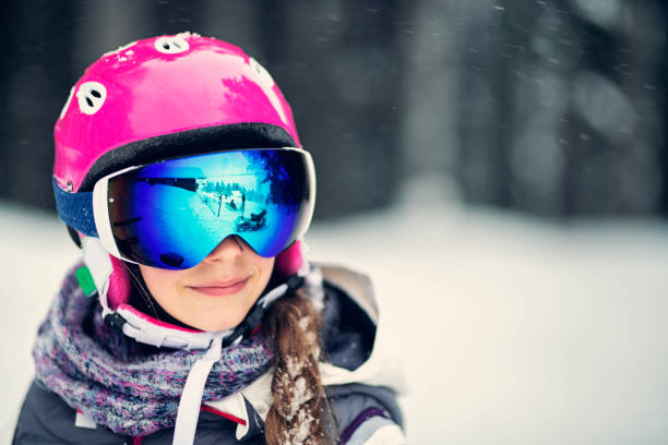 Portrait of a teenage girl skiing Happy little girl skiing on a beautiful winter day. Portrait of the girl wearing ski helmet. Shot with Nikon D850 ski goggles stock pictures, royalty-free photos & images