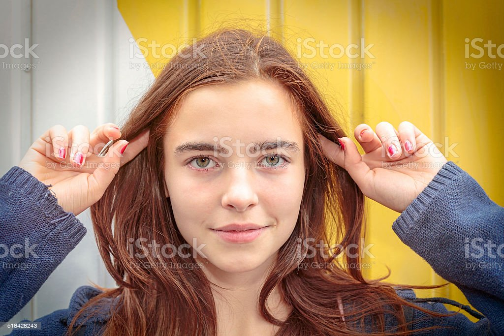portrait of a teenage girl with fingers in the hair stock photo