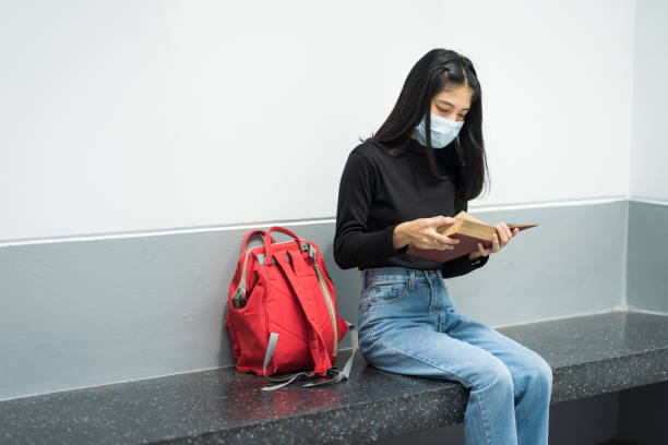 Portrait of a teenager college student wears face mask while reading book in college campus to prevent COVID-19 pandemic. stock photo