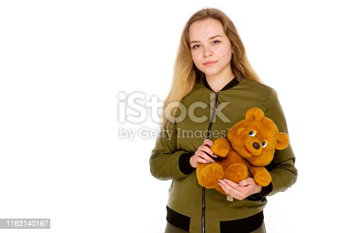 514727472istockphoto Portrait of a teenager teen girl with a teddy bear in her hands on a white background. 1163140167