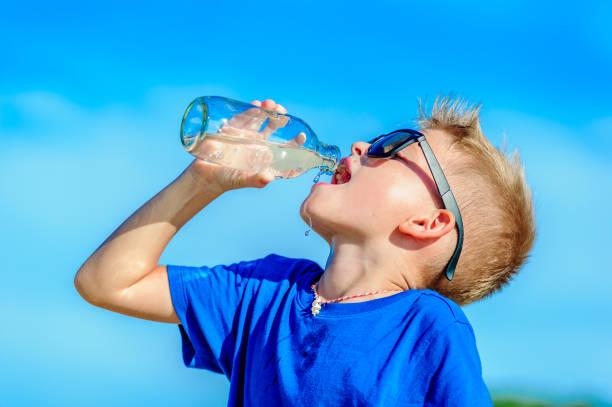 渴了英俊的男孩在沙漠的熱帶海灘上太陽鏡飲用水中的肖像 - 口渴 個照片及圖片檔