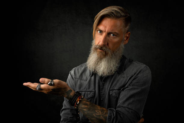 Portrait of a thoughtful bearded man who make a gesture with his left hand stock photo
