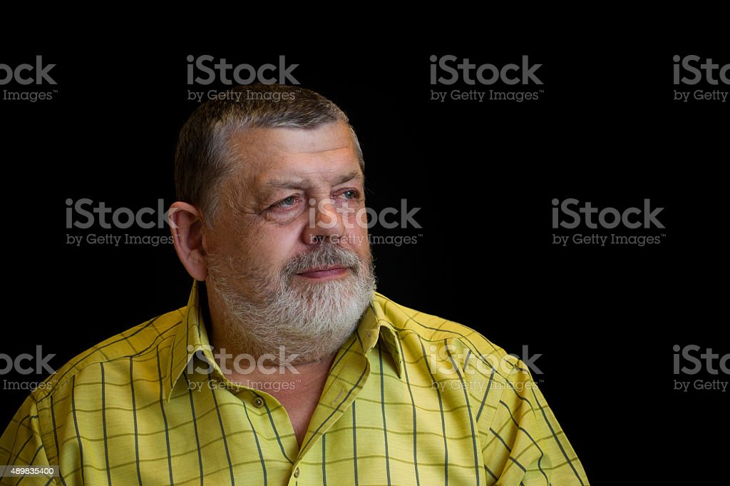 Portrait of a thoughtful senior man in yellow shirt stock photo