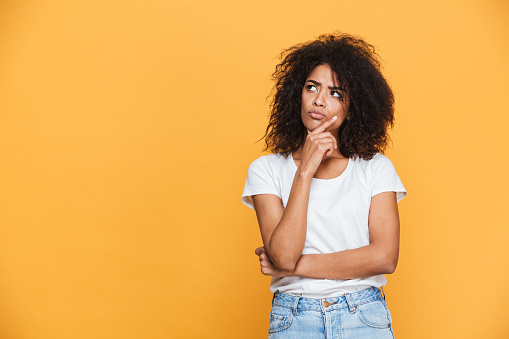 Portrait of a thoughtful young african woman looking away at copy space isolated over beige background