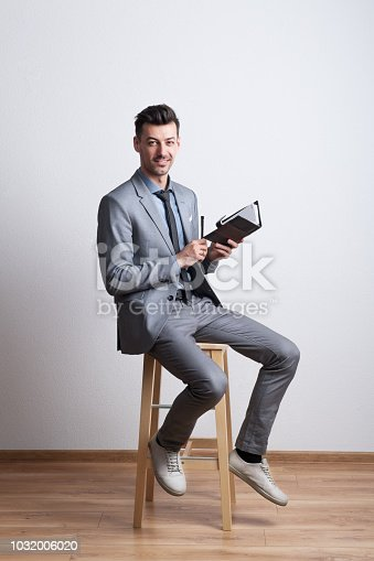 Portrait of a thoughtful young man sitting on a stool in a studio and holding a pen and a diary, planning.
