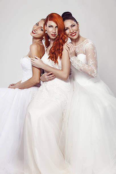 portrait of a three beautiful woman in wedding dress stock photo