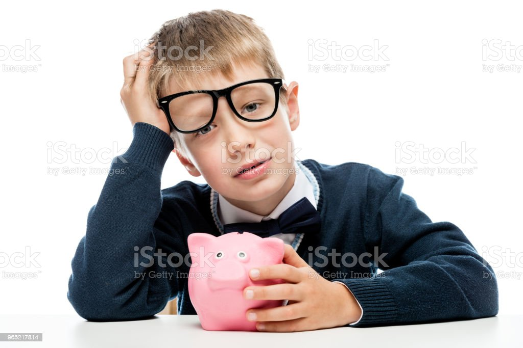 portrait of a tired boy in glasses with a piggy bank pink on a white background zbiór zdjęć royalty-free