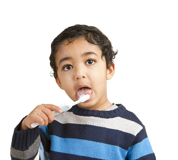 Portrait of a Toddler Brushing His Teeth, Isolated, White stock photo