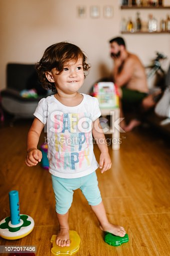544818734 istock photo Portrait of a toddler, girl, adorable baby playing color pyramid on the floor indoors, little child play, game in a room at home or kindergarten. 1072017456