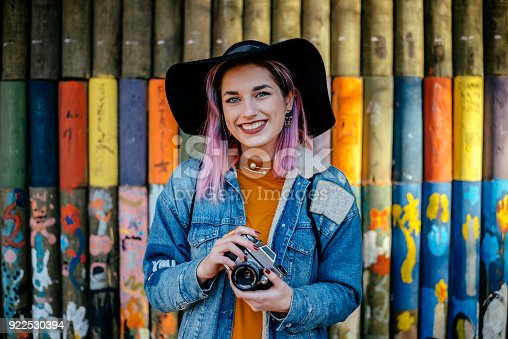 Portrait of a tourist girl with dyed hair and a hat standing in front of a painted wall.
