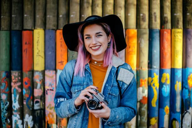 porträt von einem touristischen mädchen mit gefärbten haaren und ein hut steht vor einer bemalten wand. - coole liebessprüche stock-fotos und bilder
