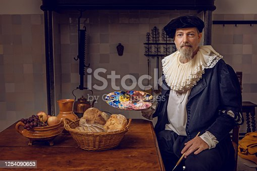Portrait of a handsome traditional dutch nobleman wearing historically correct outfit whilst sitting at a table in a typical townhouse kitchen