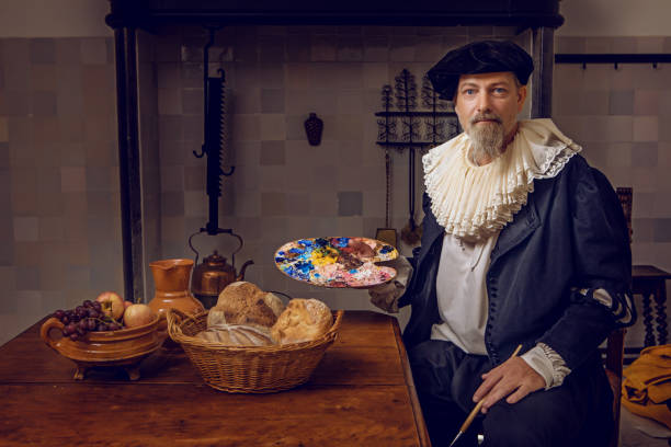 Portrait of a traditional dutch nobleman at a kitchen table Portrait of a handsome traditional dutch nobleman wearing historically correct outfit whilst sitting at a table in a typical townhouse kitchen renaissance stock pictures, royalty-free photos & images