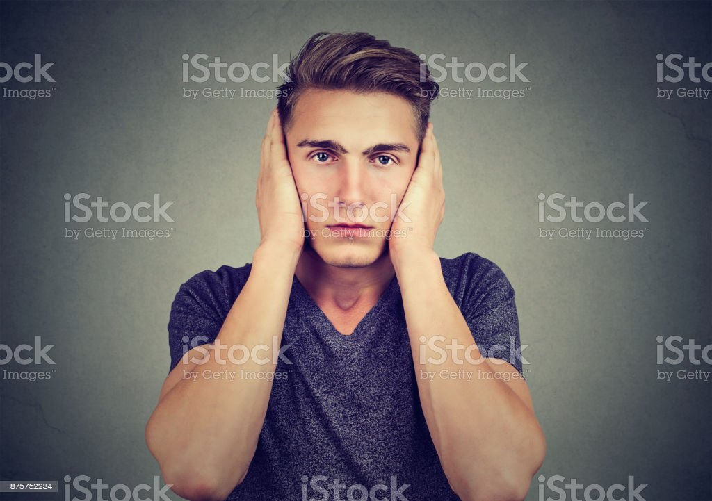 Portrait of a tranquil relaxed man covering his ears looking at camera isolated on gray background. Hear no evil concept. Human emotions stock photo
