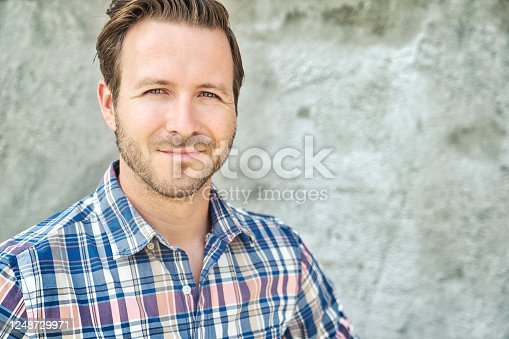 istock portrait of a trendy young man in the city concreate background 1248729971