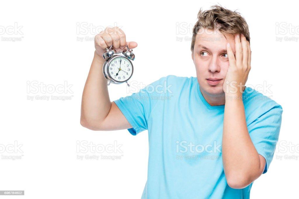 Retrato de um homem com sono perturbado com um despertador no fundo branco - foto de acervo