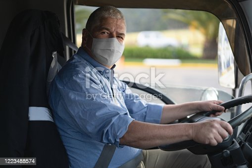 Portrait of a truck driver wearing a facemask to avoid the coronavirus while driving his vehicle - pandemic lifestyle concepts