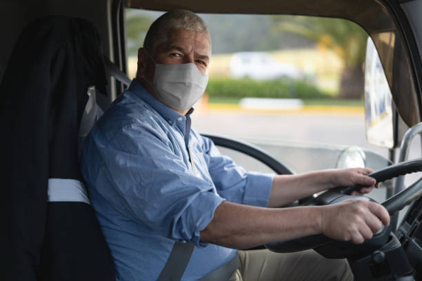 portrait of a truck driver wearing a facemask to avoid the coronavirus - servizi essenziali foto e immagini stock