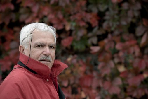 Turkish man looking at camera and wearing red jacket.