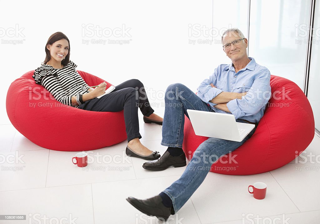 Portrait of a two office workers relaxing on bean bags royalty-free stock photo