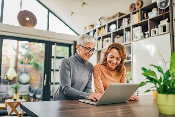 Retrato de dos mujeres de una edad diferente usando portátil en casa moderna. - foto de stock
