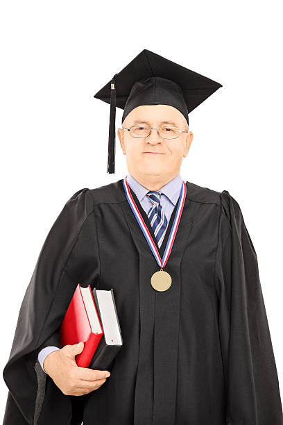 Portrait of a university dean in graduation gown posing Portrait of a university dean in graduation gown posing isolated on white background college dean stock pictures, royalty-free photos & images