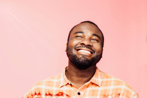 portrait of a very happy young man with big smile looking up, isolated on colorful background - carlos david stock pictures, royalty-free photos & images