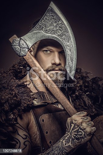 Portrait of a viking inspired barbarian warrior man holding a weapon in a studio shot