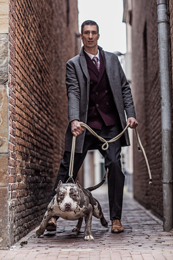 Portrait of a vintage Gangster Man with his guard dog outdoors in an old city in the daytime