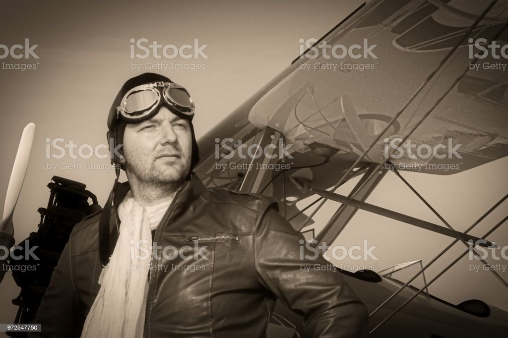 Portrait of a vintage pilot with leather cap, scarf and aviator glasses in  front of a historic airplane biplane - Portrait of a man in historical pilot  ...