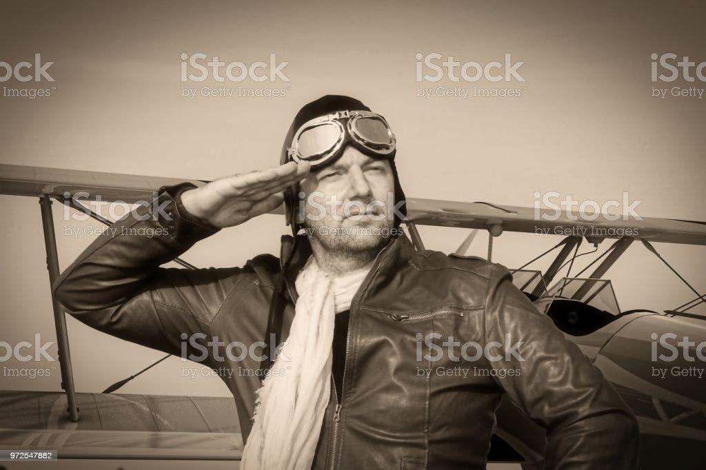 Porträt eines Vintage Piloten mit Ledermütze, Schal und Fliegerbrille vor einer historischen Flugzeug Doppeldecker - Portrait eines Mannes in historischer Kleidung pilot - Vintage alte Bild-Stil – Foto