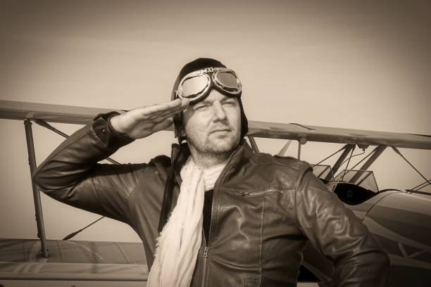 Portrait of a vintage pilot with leather cap, scarf and aviator glasses in front of a historic airplane biplane - Portrait of a man in historical pilot clothing - vintage old picture style stock photo
