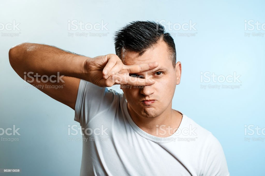 Portrait Of A White Man On A Light Background Gesture Two Fingers