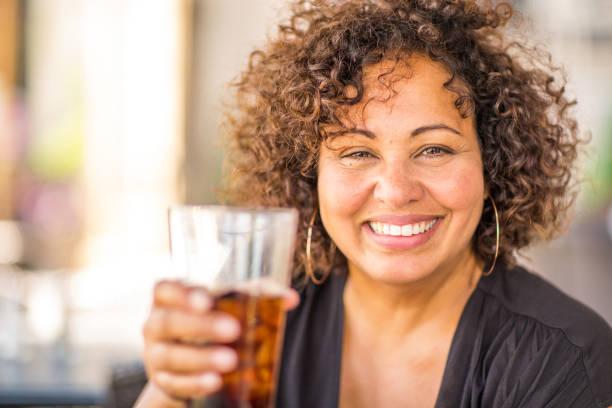 retrato de uma mulher em um restaurante que tem uma bebida. - tea drinks - fotografias e filmes do acervo